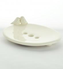 Porte-savon ovale en faïence blanche émaillée avec deux oiseaux sur le rebord. Trois trous permettent l'écoulement de l'eau et donc au savon de sécher. Poterie artisanale made in Quimper.
